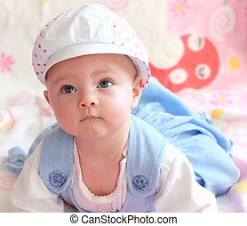 Beautiful happy thinking looking up with interest baby girl in funny hat lying  in blue dress