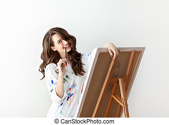 Beautiful happy woman artist posing in studio with her artwork