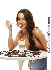 beautiful happy woman at a table with latte macchiato on white background