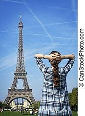 Beautiful happy woman before Paris Eiffel Tower