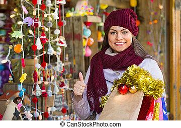 Beautiful happy woman choosing Christmas decoration