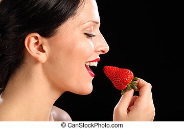 Beautiful happy woman eating red strawberry fruit