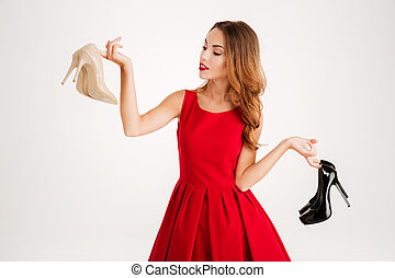 Beautiful happy woman holding high heels shoes