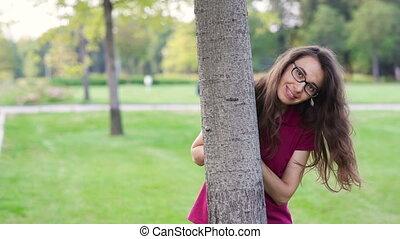 Beautiful happy woman in a park near a tree