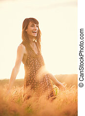 Beautiful happy woman in field at sunset