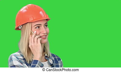 Beautiful happy woman in orange hardhat have a phone call via smartphone and smiling on a Green Screen, Chroma Key.