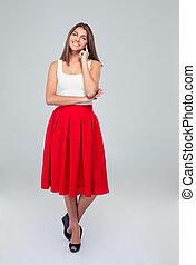 Beautiful happy woman in skirt looking at camera - Full ...
