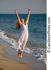 beautiful happy woman in white dress jumping up on the beach on a Sunny day