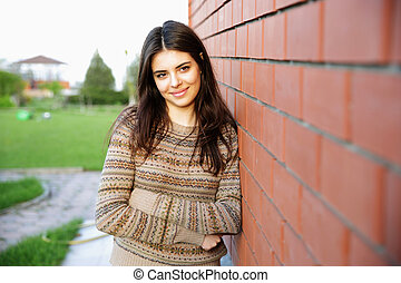 Beautiful happy woman leaning on the brick wall