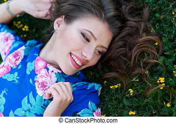 beautiful happy woman lying on the grass with yellow flowers
