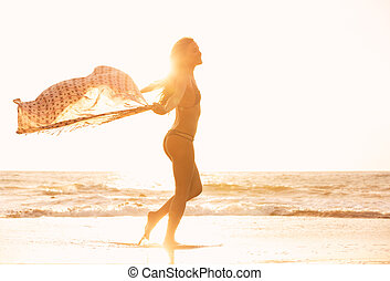 Beautiful happy woman on beach at sunset