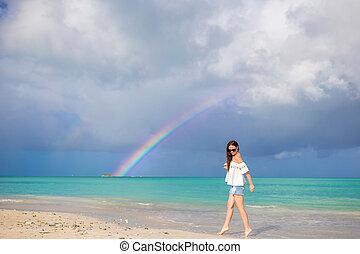 Beautiful happy woman on the beach with beautiful rainbow over the sea