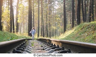 Beautiful happy woman running on railroad in deep pines forest during autumn in slowmotion. 1920x1080