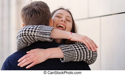 Beautiful happy woman tenderly hugging her boyfriend and saying how much she loves him while walking on the street.