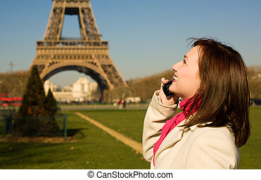 Beautiful happy woman with cell phone in Paris