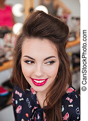 Beautiful happy woman with makeup and hairstyle in beauty salon