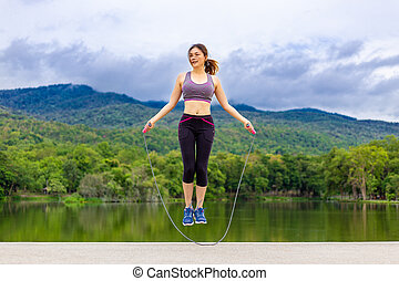 Beautiful happy young Asian woman jumping rope during her morning exercise at a lake with mountains background, healthy lifestyle