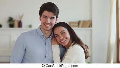 Beautiful happy young couple bonding looking at camera in apartment