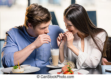 Beautiful happy young couple in love at romantic date in restaurant