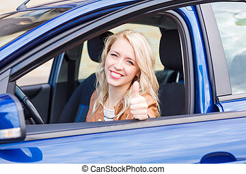 Beautiful happy young girl sitting in the car