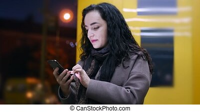 Beautiful Happy Young Pretty Woman in Brown Coat with Dark Blue Scarf and Long Dark Hair Enjoys Coffee Messaging on the Smart-phone on the background of the night or evening city.