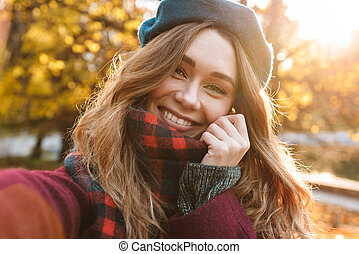 Beautiful happy young pretty woman walking outdoors in autumn spring park take a selfie by camera.