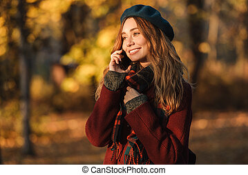 Beautiful happy young pretty woman walking outdoors in autumn spring park talking by mobile phone.