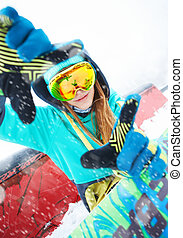 Beautiful happy young snowboarder sitting with her snowboard.
