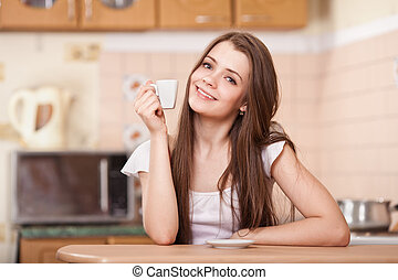 beautiful happy young woman drinking coffee at home