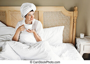Beautiful happy young woman drinking coffee in bed in hotel room or home bedroom. Stylish brunette girl in white towel enjoying morning with hot drink. Space for text