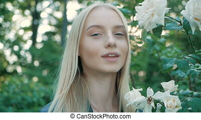 Beautiful happy young woman enjoying smell flowering spring garden