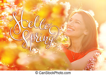 young woman enjoying smell in a flowering spring garden with letters Hello sprint