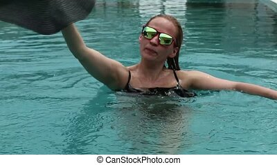 Beautiful happy young woman in sunglasses smiling and relaxing in hotel pool