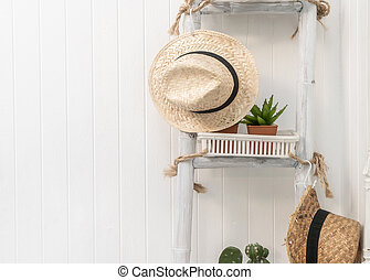 hat hanging on white stair with copy sapce