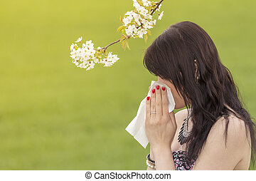 The beautiful young woman is pained by her allergy every year. She holds a tissue in her hands.