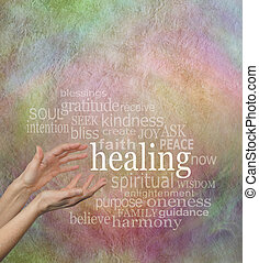 Pair of female hands reaching out to the word 'healing' surrounded by a word cloud of healing related words on a rustic stone effect pastel colored background