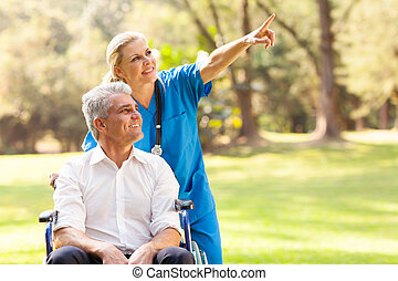healthcare worker taking disabled patient for a walk