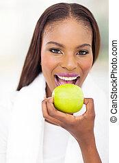 healthy black woman eating apple