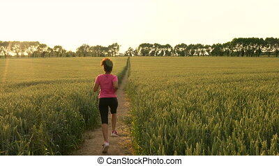 Beautiful healthy mixed race African American girl teenager female young woman runner running on path through field of barley or wheat crops at sunset
