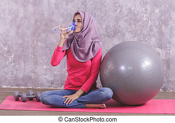 beautiful healthy woman drinking mineral water after doing yoga