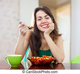 beautiful healthy woman eating veggie salad at home
