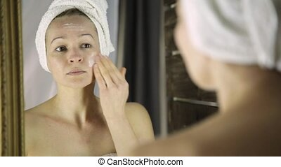 Beautiful healthy woman in a towel putting moisturizing cream on face. Skin care and home Spa