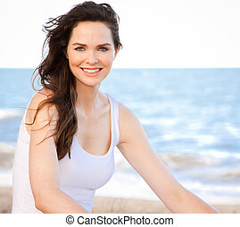 Beautiful healthy woman sitting on beach - Portrait of a ...