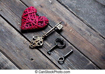 beautiful heart shaped toy and different keys on the wonderful brown wooden background