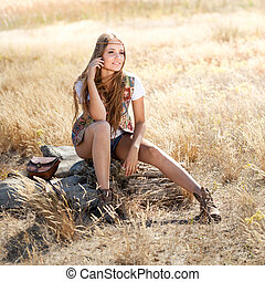 Beautiful hippie girl sitting on a tree stump