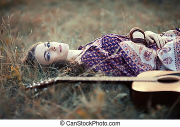 Beautiful hippie girl with guitar lying on the grass
