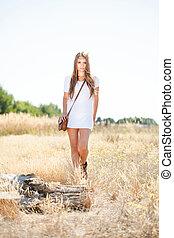 Beautiful hippie looking girl approaching a tree stump -...