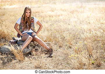 Beautiful hippie looking girl sitting on a tree stump