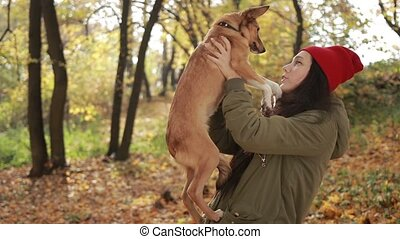 Beautiful hipster girl holding dog in autumn park