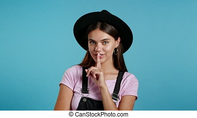 Beautiful hipster woman in hat holding finger on her lips ...